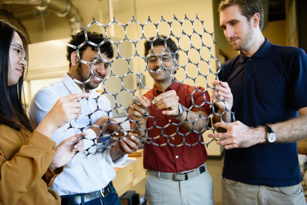 Jingyi Zhu, Ramakrishna Podila, Apparao Rao and Anthony Childress with a large-scale model of graphene superconductor material. Photo by Ashley Jones.